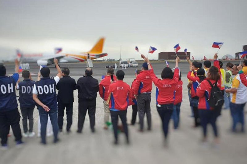 PAMPANGA. Officials and staff from the Department of Health and Department of Foreign Affairs wave the Philippine flag in welcoming the 32 repatriates from China on Sunday, February 9, 2020. (Photo courtesy of DFA Usec. Sarah Arriola)