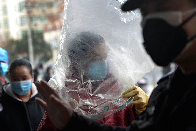 CHINA. A man wearing a protective face mask covered himself with a plastic cover before enters a supermarket in Wuhan in central China's Hubei province, Monday, February 10, 2020. (AP)
