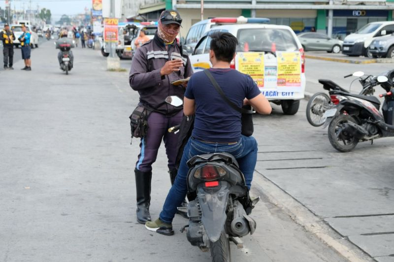 PAMPANGA. A member of the Mabalacat City Traffic Enforcement Group apprehends a motorcycle rider who violated the