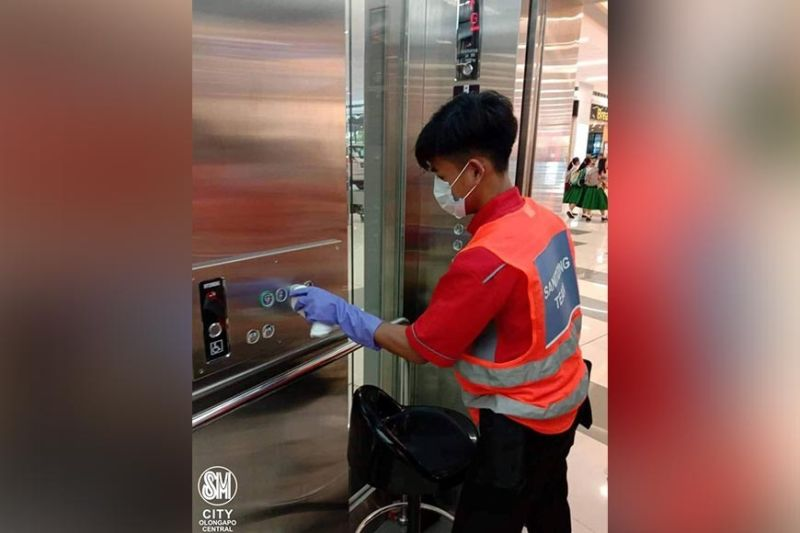 PAMPANGA. A shopping mall employee at SM City Olongapo Central cleans elevator buttons as part of the mall's preventive measures against the novel coronavirus. (Contributed photo)