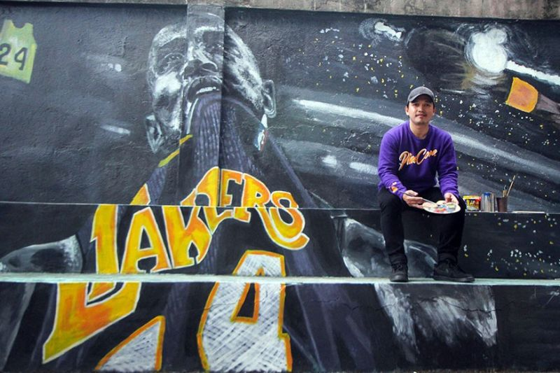 BAGUIO. Online English tutor and part time artist Bryan Flora poses in front of the mural he painted as tribute to his basketball idol, Kobe Bryant. Using his own money to buy painting materials, it took Flora a week to paint the mural at the Military Cut-off basketball court. (Photo by Jean Nicole Cortes)