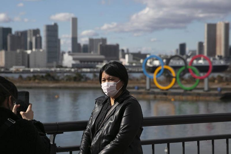 In this Jan. 29, 2020, a tourist wearing a mask poses for a photo with the Olympic rings in the background, at Tokyo's Odaiba district. Tokyo Olympic organizers repeated their message at the start of two days of meetings with the IOC: this summer's games will not be cancelled or postponed by the coronavirus spreading neighboring China. (AP file photo)