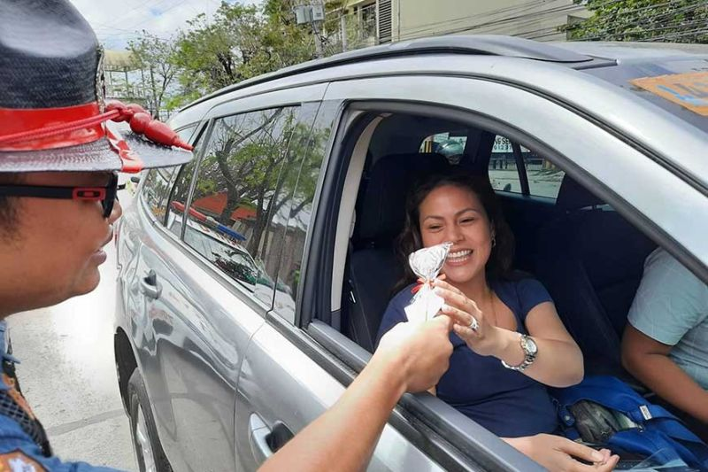 LOVE OFFERING. A member of the Highway Patrol Group 7 gives a gift to a lady motorist along V. Rama Ave., Barangay Calamba, Cebu City on Valentine's Day. (SunStar Photo / Arnold Bustamante)