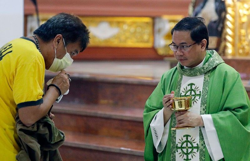 MANILA. In this February 10, 2020, photo, Catholic priest Fr. Joseph Arellano, right, looks at a man who forgot to take off his protective mask and tried to insert the host in his mouth during communion at a mass at the Minor Basilica of San Lorenzo Ruiz in Manila's Chinatown. In a popular Catholic church in Manila, nearly half of the pews were empty for Sunday Mass. The few hundred worshippers who showed up, some in protective masks, have been asked to refrain from shaking or holding hands in prayers. (AP)