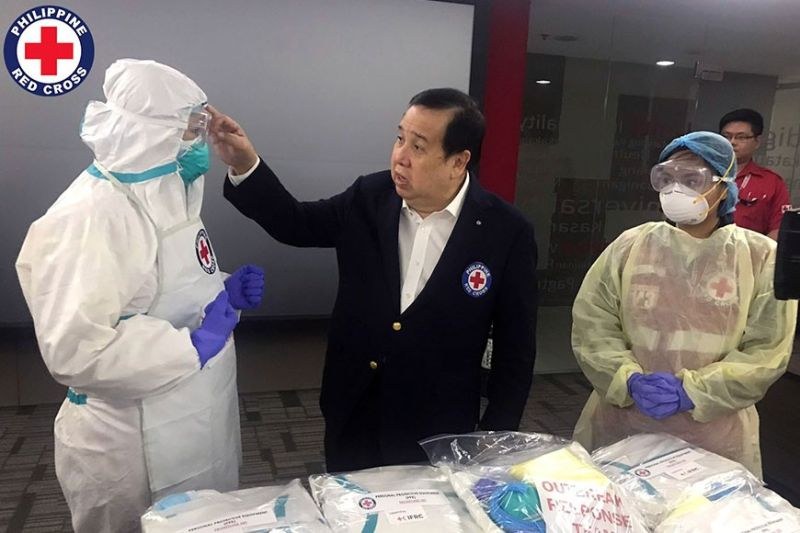 RED CROSS READY. Philippine Red Cross Chairman Richard Gordon checks a protective suit of one of his staff who will be handling cases of suspected corona virus.