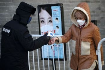 CHINA. A woman wearing a protective face mask receives a temperature check from a security guard as she enters Qianmen Street, a popular tourist spot, in Beijing, Sunday, February 16, 2020. China reported Sunday a drop in new virus cases for the third straight day, as it became apparent that the country's leadership was aware of the potential gravity of the situation well before the alarm was sounded. (AP)