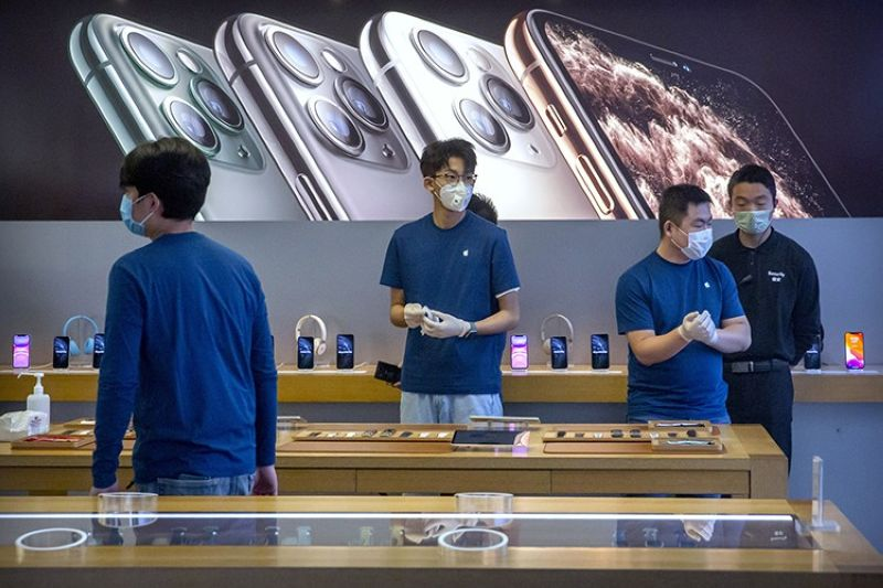In a Feb. 14, 2020 file photo, employees wear face masks as they stand in a reopened Apple Store in Beijing. Apple Inc. is warning investors that it won't meet its second-quarter financial guidance because the viral outbreak in China has cut production of iPhones. The Cupertino, California-based company said Monday, Feb. 17, 2020 that all of its iPhone manufacturing facilities are outside Hubei province, and all have been reopened, but production is ramping up slowly. (AP File Photo)