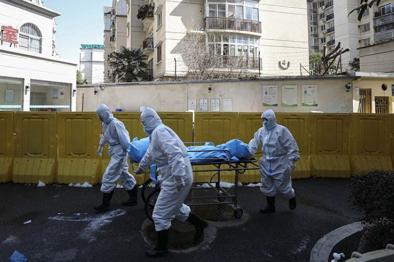 In this Sunday, February 16, 2020, photo, medical workers move a person who died from COVID-19 at a hospital in Wuhan in central China's Hubei province. Chinese authorities on Monday reported a slight upturn in new virus cases and hundred more deaths for a total of thousands since the outbreak began two months ago. <b>(AP photo)</b>