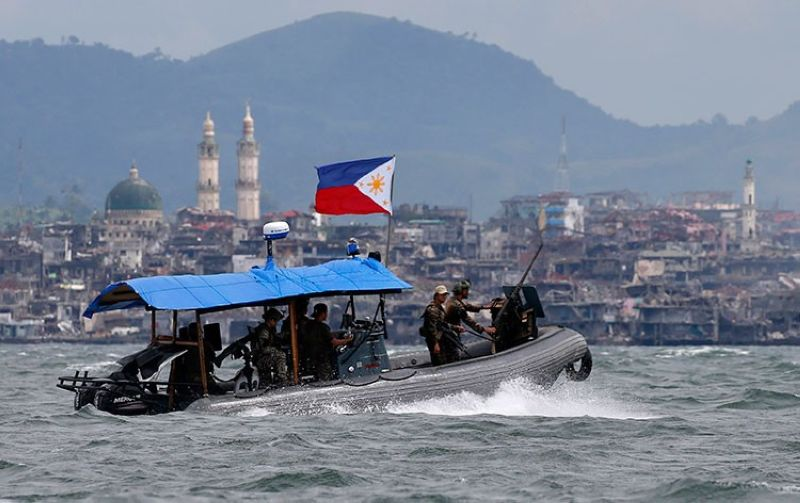 MARAWI. In this October 19, 2017, file photo, Philippine Navy commandos aboard a gunboat patrol the periphery of Lake Lanao as smoke rises from the