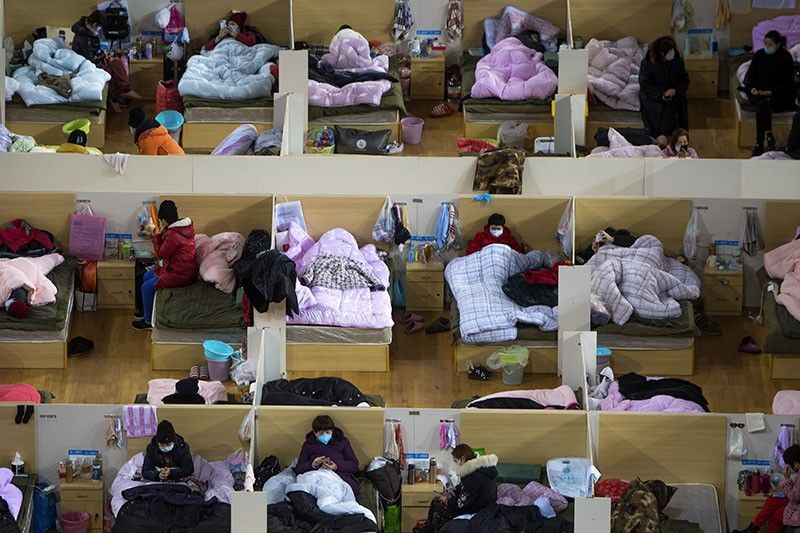 CHINA. In this Monday, February 17 photo released by Xinhua News Agency, patients infected with the coronavirus take rest at a temporary hospital converted from Wuhan Sports Center in Wuhan in central China's Hubei Province. China reported thousands new virus cases and more deaths in its update Tuesday on a disease outbreak that has caused milder illness in most people, an assessment that promoted guarded optimism from global health authorities. (AP)