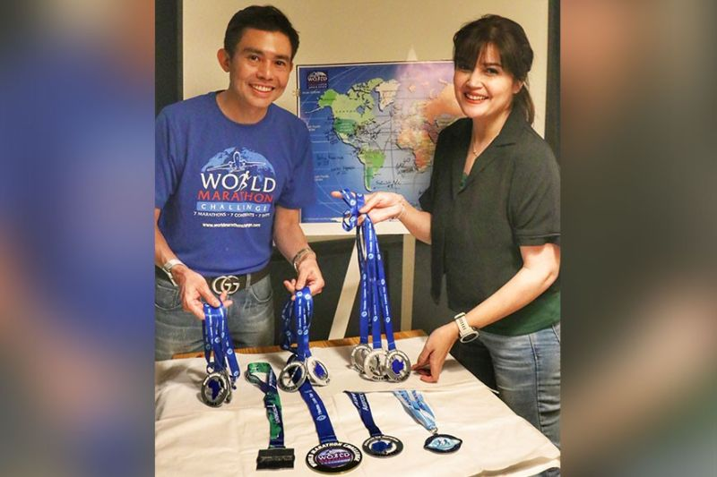 """TRIPLE 7. Ophthalmologist Potenciano """"Yong"""" Larrazabal III (left) and his wife Donna Cruz-Larrazabal pose with the World Marathon Challenge medals . (Sunstar Photo / Amper Campaña)"""