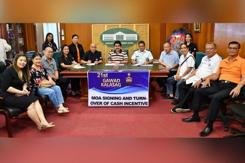 Mayor Evelio Leonardia signs as witness the MOA between the DND-OCD, represented by DND-OCD-6 regional director Jose Roberto Nuñez, and the Amity Volunteer Fire Brigade, represented by fire chief Mike Gorne, for the P300,000 cash incentive for AVFB after winning at the 21st Gawad Kalasag Awards. Also witnessing the signing are Vice Mayor El Cid Familiaran, Councilors Cindy Rojas, Renecito Novero, and Ana Marie Palermo, Executive Assistant Jose Ma. Vargas, Negros Occidental Filipino–Chinese Amity Club executive vice chairman Roger Yap, corporate secretary Crispin Chua, and honorary chairman Yip Ying Wun.PR