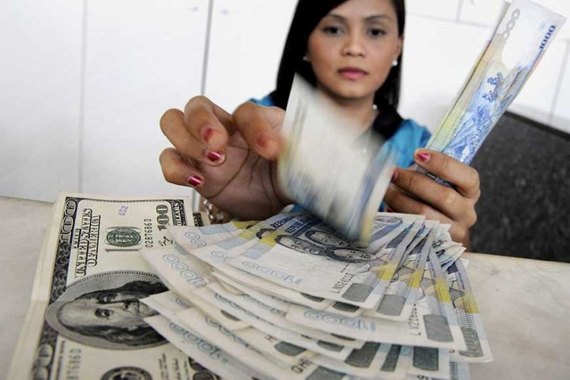 STEADY. A bank teller counts Philippine peso for a client selling US dollars. The Cebu Bankers Club is optimistic that money sent home by overseas Filipino workers will not be severely affected by the global tensions abroad, such as the Covid-19 global outbreak. (AP photo)
