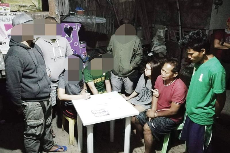 TALISAY'S ANTI-DRUG CAMPAIGN. Francisco Luage (in red shirt) and his daughter, Sangguniang Kabataan chairman Guendolyn Luage (seated beside him) of Barangay Lawaan, Talisay City are arrested during an anti-drug operation conducted by the Talisay City Police on Wednesday, Feb. 19, 2020. About P600 worth of shabu was allegedly found in their house during the raid. Francisco, a former chief of barangay tanods, denies he or Guendolyn are into the drug trade. (TALISAY CITY POLICE)