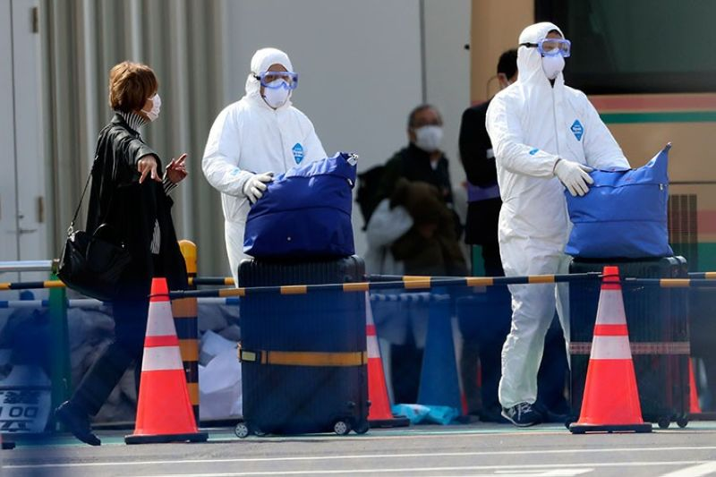 JAPAN. Officials in protective suits help a passenger disembark from the quarantined Diamond Princess cruise ship anchored at a port in Yokohama, near Tokyo, Thursday, February 20, 2020. Passengers tested negative for Covid-19 started disembarking since Wednesday. (AP)