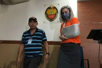 MANILA. Jennifer Talbot wears a face mask as she is escorted by an agent of the National Bureau of Investigation Wednesday, February 19, 2020 in Manila, Philippines. (AP)