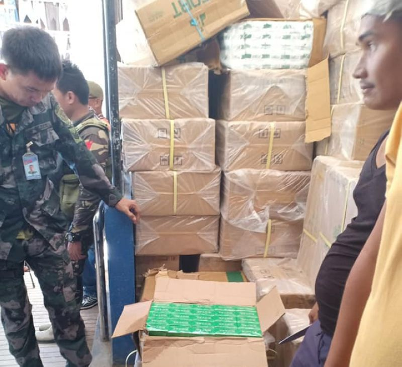 ZAMBOANGA. A policeman inspects the smuggled cigarettes seized on Thursday, February 20, in San Vicente Village, Tungawan, Zamboanga Sibugay. (Contributed photo)