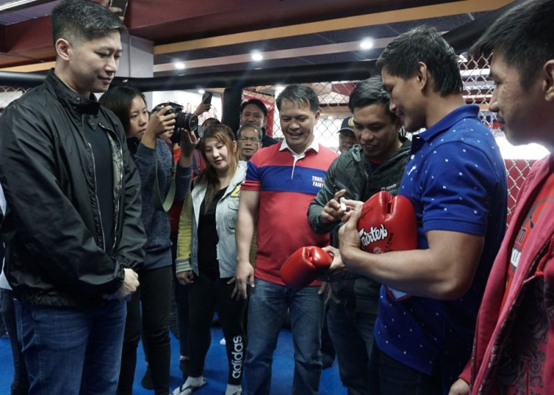 BAGUIO. Team Lakay fighters Eduard Folayang, Kevin Belingon, and Geje Esutaquio with coach mark Sangiao sign the gloves as a token to Benguet caretaker Eric Go Yap during his visit in their gym. (Photo by Roderick Osis)