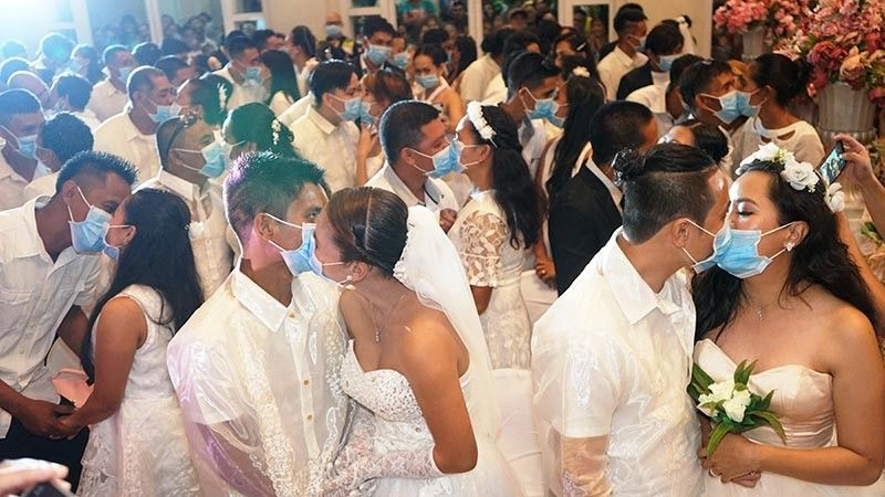 BACOLOD. The mass wedding has turned into a 'mask' wedding for the 220 couples. The highlight of the event is when all grooms kissed their brides with the face mask on. (Photo by Bacolod City PIO)