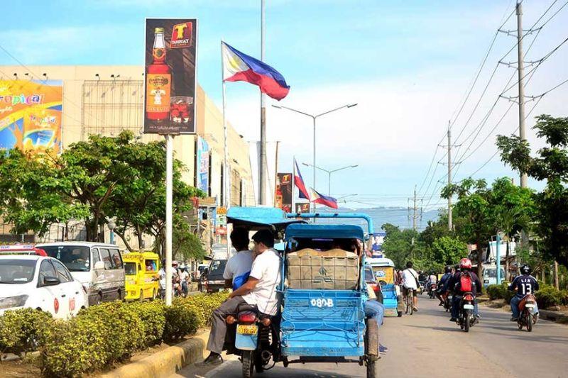 DAILY TRAFFIC. A tricycle traverses  U.N. Avenue, Mandaue City, alongside four–wheeled vehicles.  (SunStar Photo / Allan Cuizon)