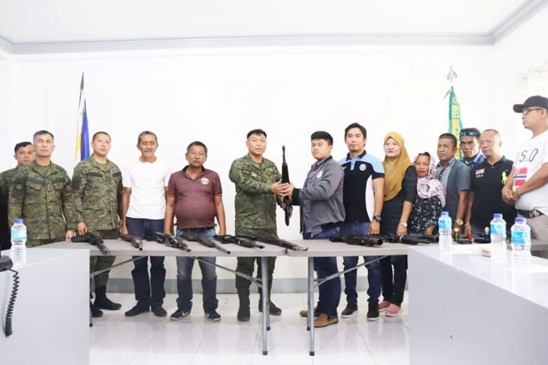 ZAMBOANGA. Colonel Joel Mamon, deputy commander of the Army's 601st Infantry Brigade (in military uniform), receives a rifle in a ceremony that saw the surrender of 11 loose firearms on Friday, February 21, by the village officials of Talitay, Maguindanao. (Contributed photo)