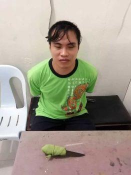 NANUNGGAB: Si Martin Fernandez, 26, nadakpan sa kapulisan sa Talisay City human niya pangdunggaba ang iyang mga ginikanan gamit ang kutsilyo (naa sa lamesa). (TALISAY CITY POLICE STATION)