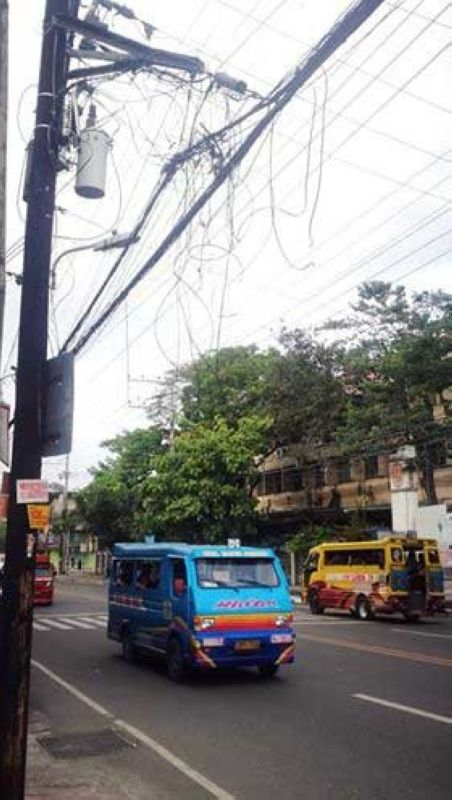 TANGLED. These spaghetti wires and drop wires along M.J. Cuenco Ave. are not only unsightly but may also pose danger to unknowing pedestrians and motorists, especially those driving large heavy equipment. (SunStar Foto / Allan Cuizon)