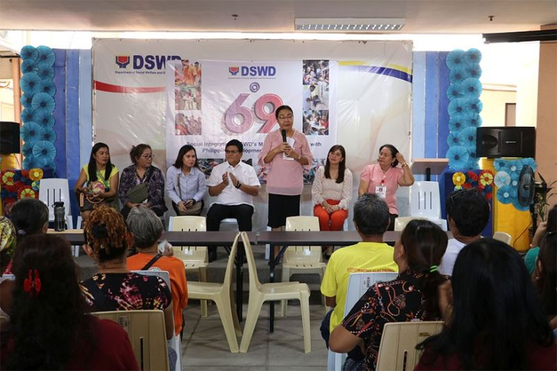 GIVING AID. Department of Social Welfare and Development 7 Director Rebecca Geamala (standing) and Cebu City Mayor Edgardo Labella (seated in white shirt) lead the distribution of financial aid to displaced sidewalk vendors on Jan. 21, 2020. (Contributed Photo)
