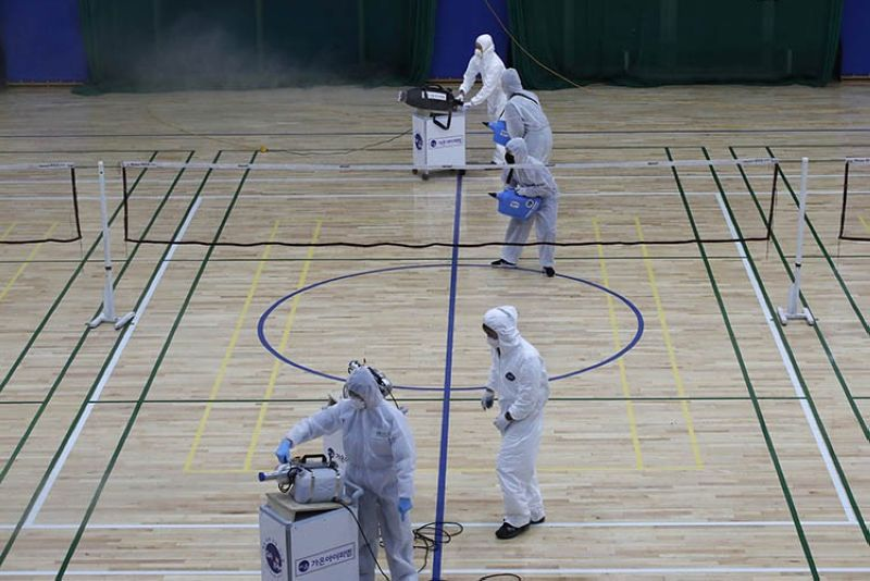 Workers in protective suits spray disinfectant as a precaution against the COVID-19 at an indoor gymnasium in Seoul, South Korea, Tuesday, Feb. 25, 2020. China and South Korea on Tuesday reported more cases of a new viral illness that has been concentrated in North Asia but is causing global worry as clusters grow in the Middle East and Europe. (AP Photo)