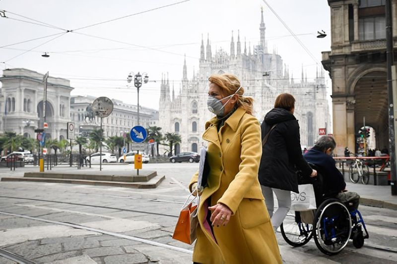 ITALY. A woman wears a sanitary mask in downtown Milan, Italy, Tuesday, February 25, 2020. (AP)