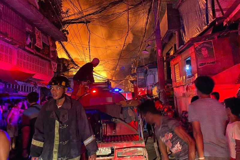 THROUGH THE FIRE. Fire fighters and residents in Barangay Suba are engaged in a frenzy of dousing the flames in a fire that hit a residential area in Sitio Sto. Niño, Barangay Suba last Feb. 26. (Sunstar Photo / Benjie Talisic)