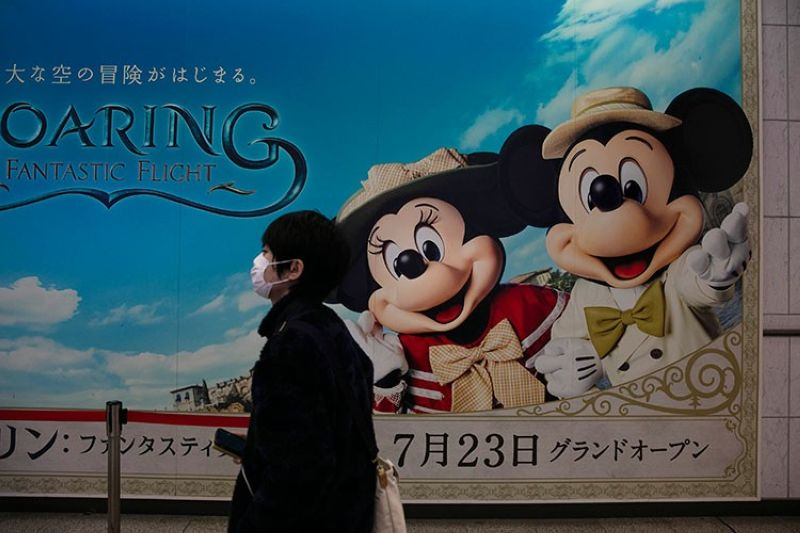 TOKYO. A man wearing a mask walks past an advertisement for the Tokyo Disney Resort at a train station in Urayasu, near Tokyo, Friday, February 28, 2020. The amusement park will be closed from February 29 until March 15 in an effort to prevent the spread of Covid-19. (AP)