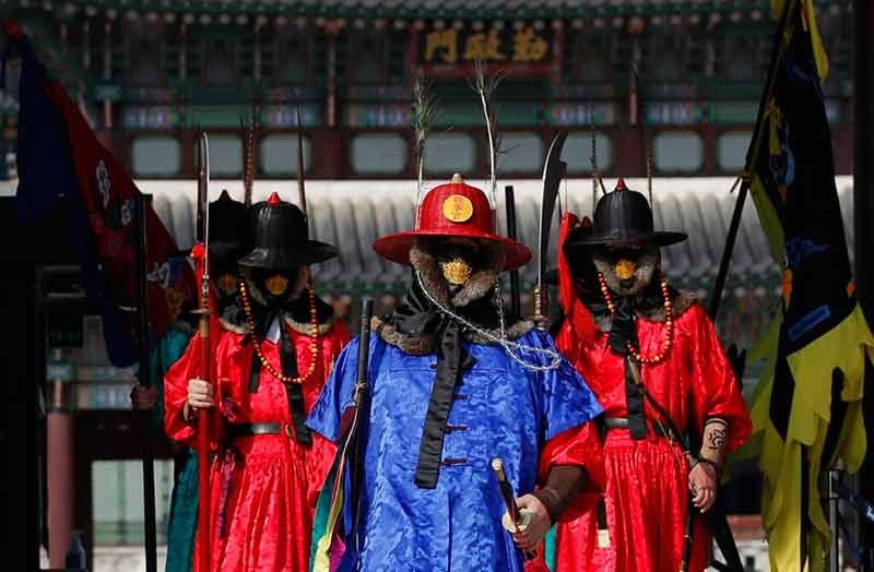 "SOUTH KOREA. Officials wearing traditional guard uniforms and protective face masks walk at the Gyeongbok Palace, the main royal palace during the Joseon Dynasty and one of South Korea's well known landmarks in Seoul, South Korea, Saturday, February 29, 2020. The coronavirus outbreak's impact on the world economy grew more alarming on Saturday, even as President Donald Trump denounced criticisms of his response to the threat as a ""hoax"" cooked up by his political enemies. (AP)"