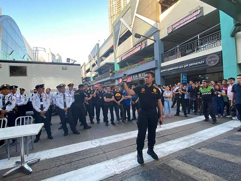 MANILA. A security officer at V-Mall holds up a mobile phone to show hostage taker Archie Paray the proceedings outside the mall on March 2, 2020. (Photo by Third Anne Peralta-Malonzo)