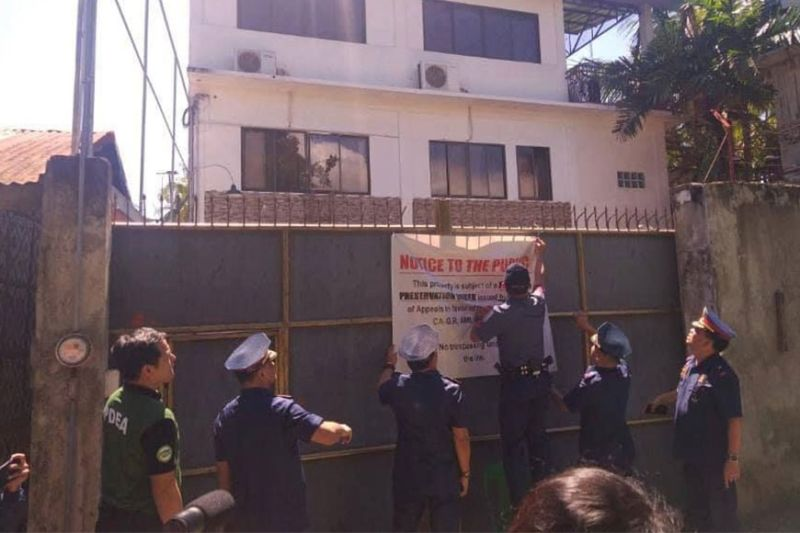 """FREEZING PROPERTY. Law enforcers implement the freeze order issued by the Court of Appeals on one of the houses of alleged """"drug queen"""" Jocelyn """"Joy"""" Encila in Consolacion, northern Cebu on Monday, March 2, 2020. (Contributed Photo )"""