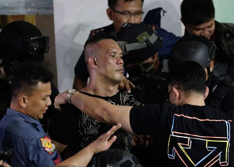 MANILA. Archie Paray (center) is escorted by police shortly after releasing all his hostages at the V-Mall in Manila on Monday, March 2, 2020. (AP)