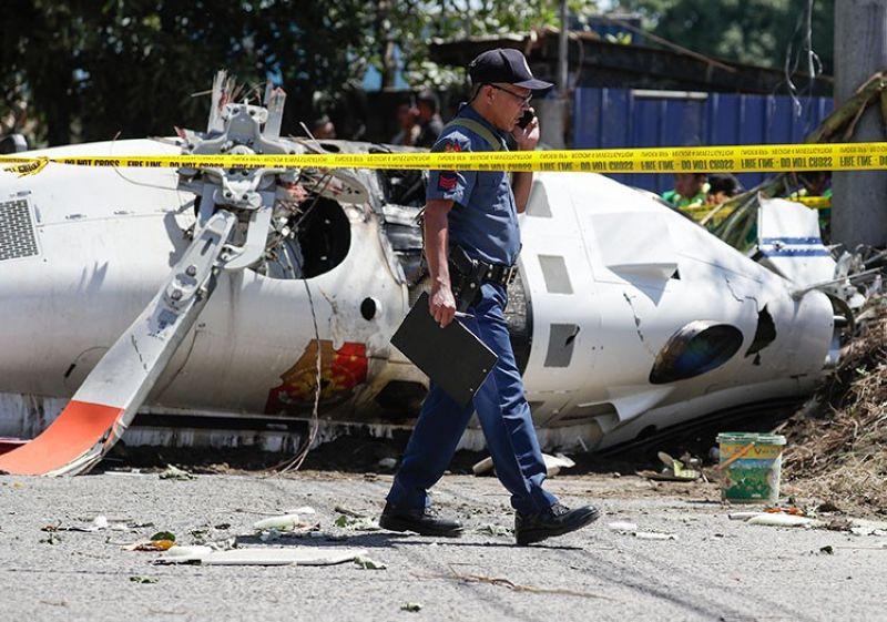MANILA. An investigator walks beside a police helicopter that crashed in San Pedro, Laguna, Thursday, March 5, 2020. (AP)