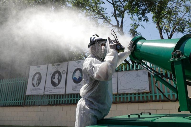 A worker in protective suit controls a big disinfectant spray as they sanitize a school which has suspended classes as a precautionary measure against a new coronavirus in San Juan City, Manila, on Monday, March 9, 2020. President Rodrigo Duterte has declared a state of public health emergency throughout the country after health officials confirmed over the weekend the first local transmission of the new coronavirus. (AP)