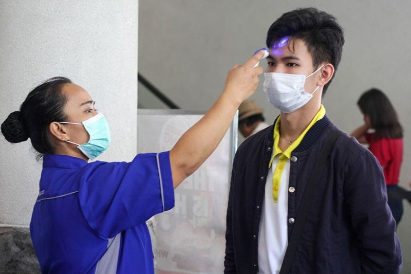 BAGUIO. A worker in Baguio City screens mall goers with their thermometers to check their temperature before allowing them to enter the vicinity as precautionary measure against Covid-19. (Photo by Jean Nicole Cortes)