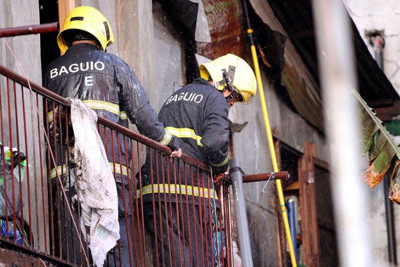 Two firemen from the Baguio City Fire Department contain the blaze which damaged an old house at Lourdes Extension Barangay in Baguio City late after noon Tuesday, March 10, 2020. Bureau of Fire Protection–Cordillera said for the first two months of 2020 until the first week of March, P11.5 million were damaged by fire. (Photo by JJ Landingin)