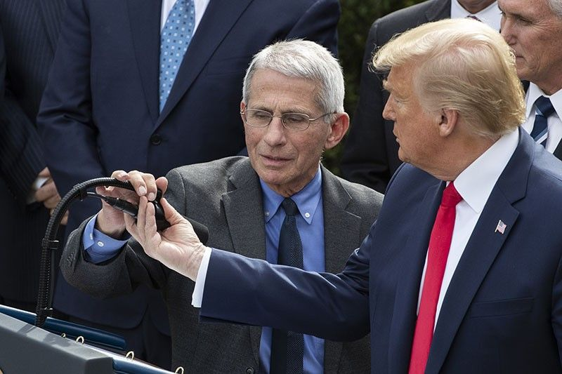 WASHINGTON. President Donald Trump assists Dr. Anthony Fauci, director of the National Institute of Allergy and Infectious Diseases with the microphone as he speaks during a news conference about the coronavirus in the Rose Garden at the White House, Friday, March 13, 2020, in Washington. (AP)