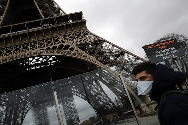 PARIS. A man wearing a mask walks pasts the Eiffel tower closed after the French government banned all gatherings of over 100 people to limit the spread of the virus Covid-19, in Paris, Saturday, March 14, 2020. For most people, the new coronavirus causes only mild or moderate symptoms. For some it can cause more severe illness, especially in older adults and people with existing health problems. (AP)
