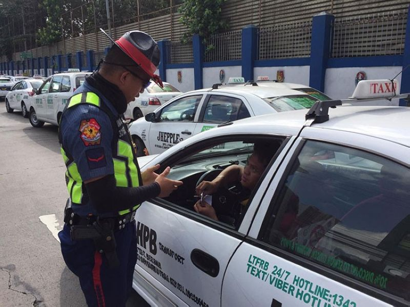 RIZAL. A police officer advises a taxi driver to suspend operations as an enhanced community quarantine takes effect in Luzon on March 17, 2020. (Photo by Third Anne Peralta-Malonzo)