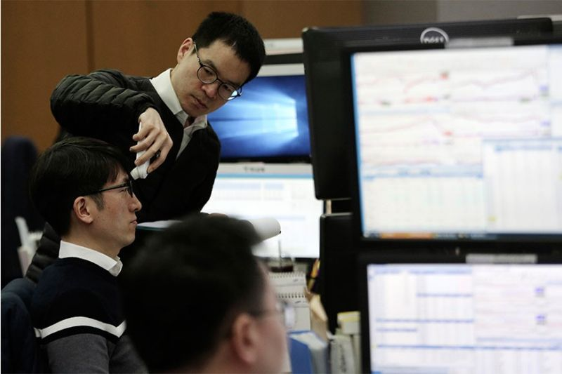 PERFORMANCE. A currency trader checks the temperature of his colleague at the foreign exchange dealing room of the KEB Hana Bank headquarters in Seoul, South Korea, Tuesday, March 17, 2020. Shares have fallen in most Asian markets after the US stock market plunged to its worst day in more than three decades. (AP PhOTO)