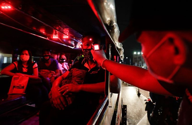 MANILA. A police officer checks the temperatures of passengers inside a jeepney at a checkpoint as part of a precautionary measure against the spread of the new coronavirus in Manila Monday March 16, 2020. (AP)