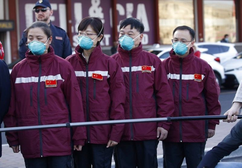 Medics and paramedics from China arrive at the Malpensa airport of Milan, Wednesday, March 18, 2020. Some 37 between doctors and paramedics were sent along with some 20 tons of equipment, and will be deployed to different hospitals in Italy's most affected area. For most people, the new coronavirus causes only mild or moderate symptoms. For some it can cause more severe illness, especially in older adults and people with existing health problems.  (AP Photo/Antonio Calanni)
