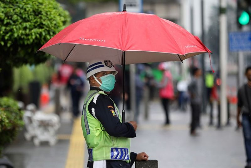 INDONESIA. A security guard wears a face mask under an umbrella during a light rain in Jakarta, Indonesia, Wednesday, March 18, 2020. Indonesia's capital city announced a lockdown of all tourist destinations and entertainment as well as the closing all of its public schools during the global coronavirus outbreak. (AP)