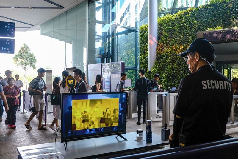 SINGAPORE. In this March 14, 2020, photo, a security personnel views a thermal screening monitor as visitors enter Gardens by the Bay in Singapore. (AP)