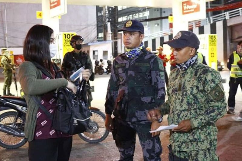 CAGAYAN DE ORO. A policeman asks for the ID from a woman during the first night of the curfew implementation of the city. (Photo courtesy of CIO)
