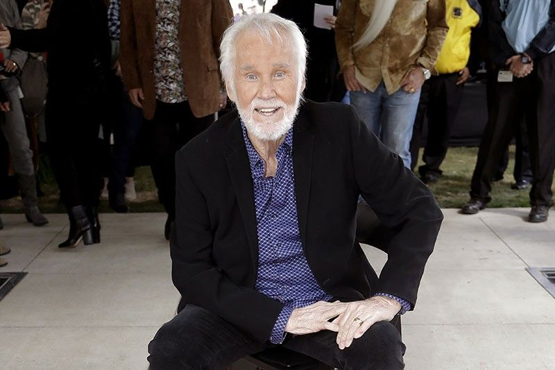 "NASHVILLE, TENNESSEE. In this Oct. 24, 2017 file photo, Kenny Rogers poses with his star on the Music City Walk of Fame in Nashville, Tenn. Actor-singer Kenny Rogers, the smooth, Grammy-winning balladeer who spanned jazz, folk, country and pop with such hits as ""Lucille,"" ""Lady"" and ""Islands in the Stream"" and embraced his persona as ""The Gambler"" on record and on TV died Friday night, March 20, 2020. He was 81. (AP)"